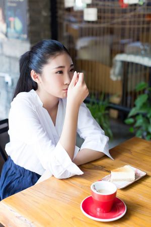 Chinese student eating dessert in a cafe photo
