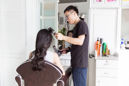 meticulous: in beauty salons clubs, and professional hair stylist to the girl in hair design Stock Photo