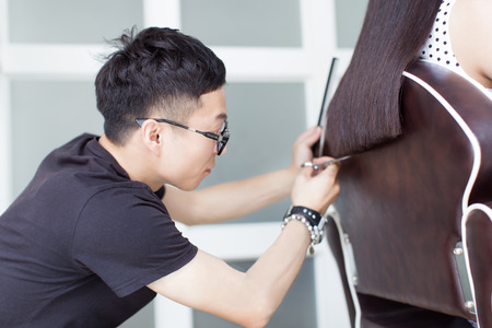 meticulous: china professional hair stylist, at a pretty girl trim long hair Stock Photo