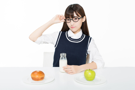 girl sitting in a classroom, apples and oranges arrayed on the desk as well as milk. Reklamní fotografie