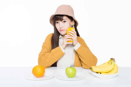 girl sitting in a classroom, apples and oranges arrayed on the desk as well as juice.