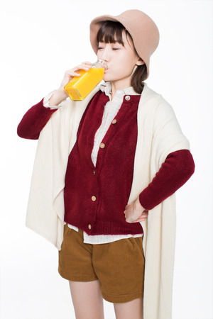 cute girl holding a bottle of juice, standing on a white background in studio