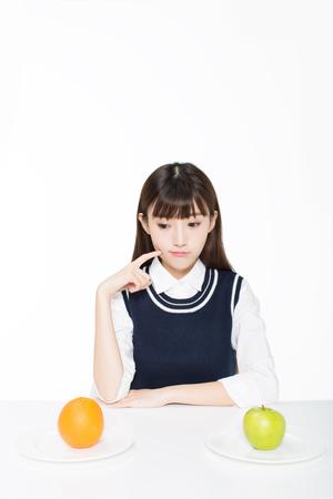 책상에 배열 된 교실, 사과, 오렌지에 앉아있는 소녀