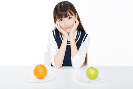 girl sitting in a classroom, apples and oranges arrayed on the desk Standard-Bild