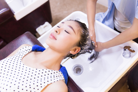 hair stylist: chinese salon stylist shampooing hair of client before haircut Stock Photo