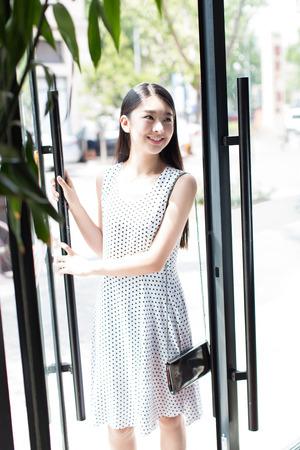 거리를 산책하는 흰 드레스를 입고 아름 다운 중국 소녀,