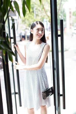 beautiful chinese girl wearing a white dress, walking in the streets
