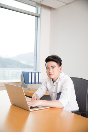 fashion handsome boy, wearing a white shirt, is the companys staff