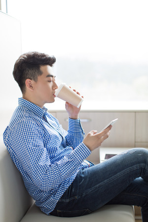 drink coffee: chinese young and handsome young man, wearing a blue shirt Stock Photo