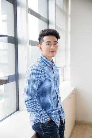 chinese young and handsome young man, wearing a blue shirt Reklamní fotografie
