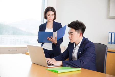 직장에서 자신의 조수로 말하는 중국 젊은 잘 생긴 보스