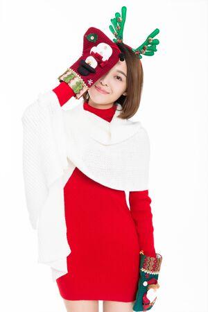 Young woman wearing reindeer antler with christmas socks, studio shot. Banco de Imagens