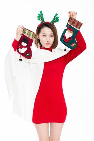 Young woman wearing reindeer antler holding christmas socks, studio shot.
