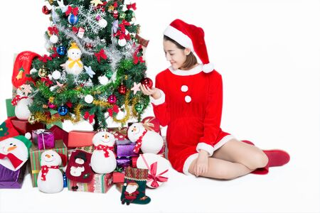 Pretty girl is sitting next to Christmas tree on white background 스톡 콘텐츠