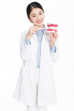 Young woman holding a dental teeth model and demonstrating to brush teeth