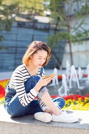 woman using phone on park bench by city garden. 스톡 콘텐츠