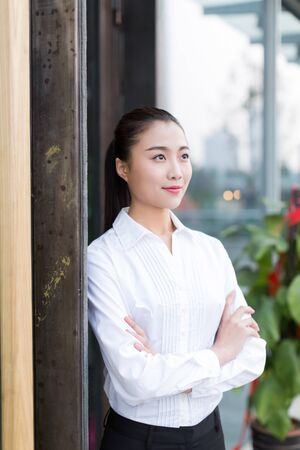pretty chinese girl wearing a white shirt, standing at office building doorway