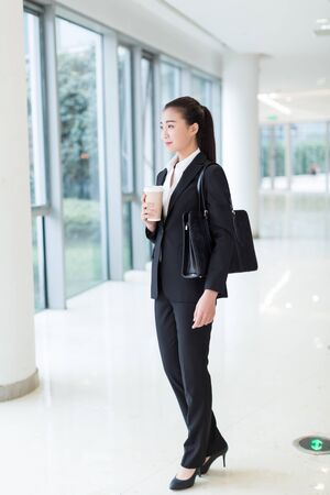 pretty girl wearing a black suit, standing in office building