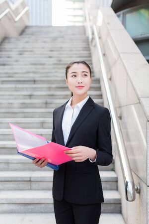 young female secretary wearing a black suit holding a folder