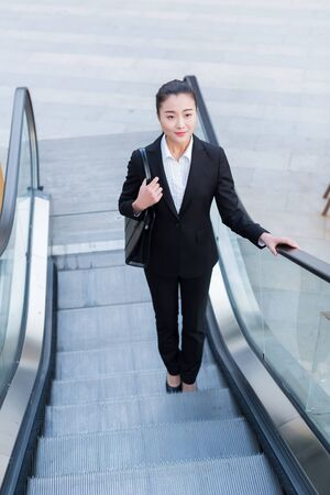 young female secretary wearing a black suit, carrying a briefcase