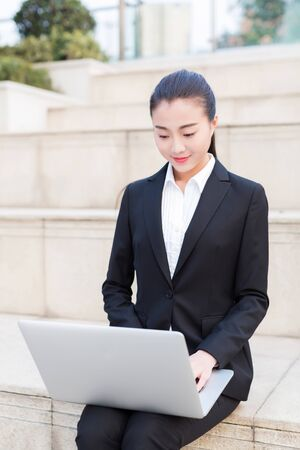 pretty girl is a civil servant, using laptop outdoors Stockfoto