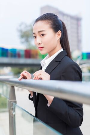 pretty chinese girl, dressed sring business attire standing on the bridge