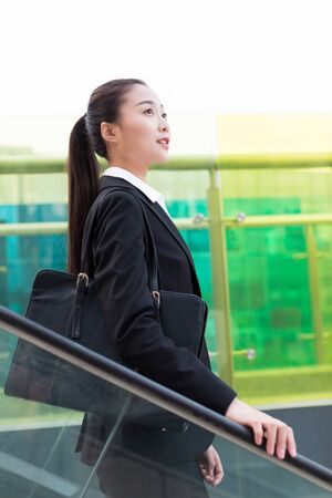 girl wearing a black suit, the elevator in the central business district