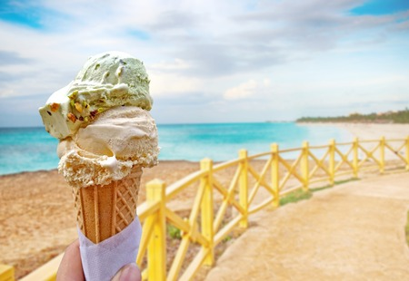 Hand is holding the vanilla ice cream.This is situated in tropical resort in Caribbean. Stock Photo