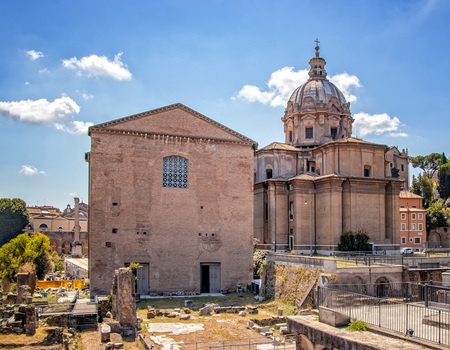Vespasian Forum, also known as the Temple of Peace,. It is in Roman Forum around the Colosseum in Rome Italy. There is sunny day with blue sky and white clouds.
