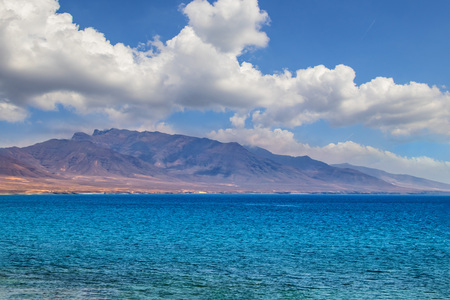 View of the hill on the island Fuerteventura near Morro Jable, Canary islands, Spain. There is clear blue water and beautiful sky. 版權商用圖片