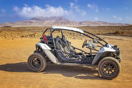 Buggy blanc dans le désert de pierre et de sable sur l'île volcanique de Fuerteventura, îles Canaries, Espagne. En arrière-plan, le ciel bleu. Banque d'images