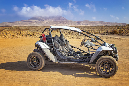 White buggy in stone and sandy desert on volcanic island Fuerteventura, Canary islands, Spain. In the background is blue sky.