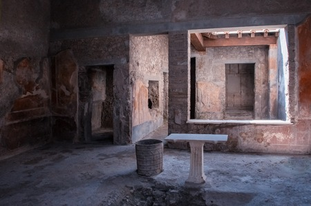The view in the ruin of house in Pompei. It is antique historical city in Italy in Eruope. There is stone table and floor. door and window.