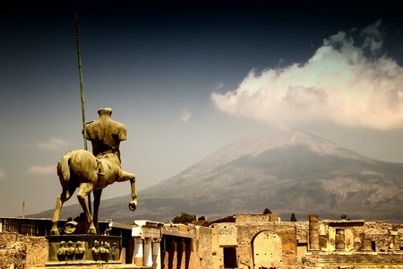 The stone statue of the roman hero in the middle of Pompei. Behind it is a view of the volcano Vesuvius. It is situated in historical area in Italy in Europe. Standard-Bild
