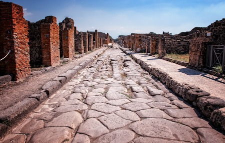 The stone road in the middle of ruins in the historical town Pompei. It is near volcano Vesuv in Italy in Europe. The city ceased to exist in 79 AD.