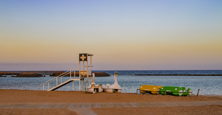 Coastguard station and pedal boats on the beach with red. It is the island of Fuerteventura- Caleta de Fuste. It's in the Canary Islands. There is beautiful sunset. Stock Photo
