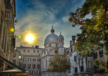 The beautiful white church in Venice in Italy. There are beautiful sunset and blue sky with white clouds.