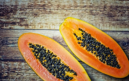 Fresh papaya imported from Africa lies on a wooden table. It is cut in half and inside there are black seeds. Stock fotó
