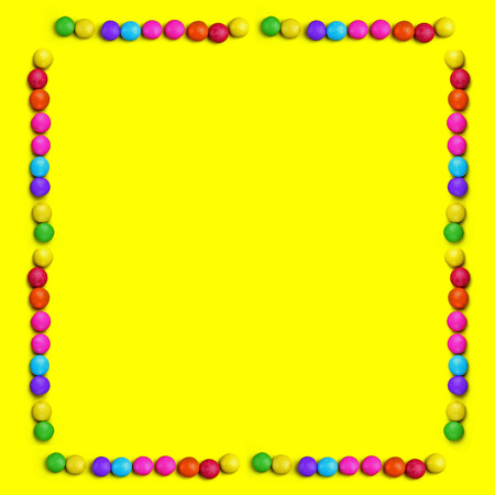 Yellow background with frame of Colorful chocolade smarties . It is can be banner or universal happy background. Summer background with chocolade sweet food. Stockfoto