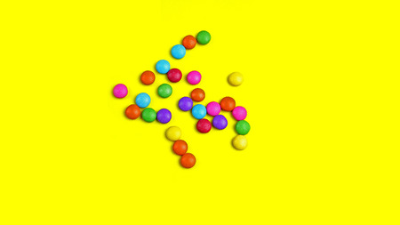 Colorful chocolade smarties on the yellow background. Summer background with chocolade sweet food.