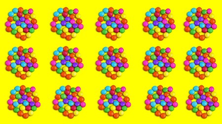 Colorful chocolade smarties on the yellow background with many chocolade bombones. It is circle shape. Summer background with chocolade sweet food.