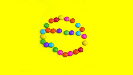 Colorful chocolade smarties on the yellow background . It is circle shape. Summer background with chocolade sweet food.