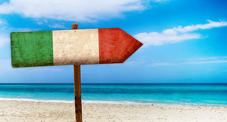 Italy flag on wooden table sign on beach background. There is beach and clear water of sea and blue sky in the background.