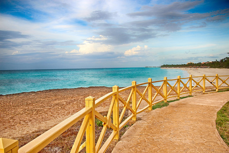 Promenade around the sea with a wooden railing and a view of the water. The clear turquoise sea of the Atlantic ocean on which are white waves. Above it is the blue sky. It's in the Caribbean in Cuba. Stockfoto