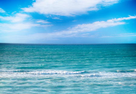 The clear turquoise sea of the Atlantic ocean on which are white waves. Above it is the blue sky. Its in the Caribbean in Cuba. There is summer time.