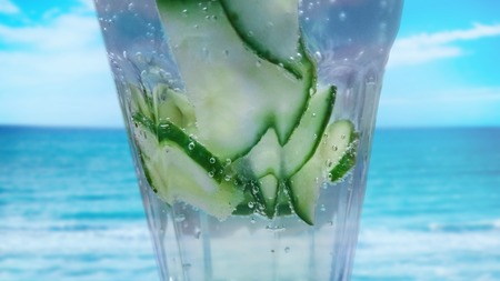Close up of Cucumber drink cocktail with fresh water. It is home made cucumber limo. In the background is turquois water sea. It is tropical background. There is summer time. Banco de Imagens