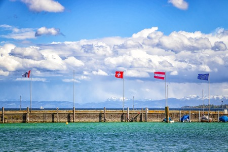 The city Constance on the Lake Constace, Bodensee. The view of port with flags. The city lies in Germany and Switzerland. In the background is big snowy mountains Alps. There is blue clear crystal water. Banco de Imagens