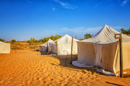 White tents in the camp of the desert Lompoul, Senegal, Africa. There is beautiful blue sky.