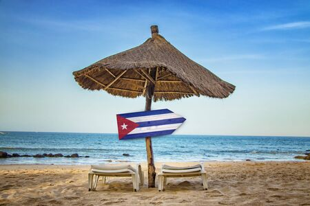 Cuban flag on wooden arrow sign. There are two sun loungers and a sun umbrella on the beach. It is a tropical paradise with a clear sea. It's summer vacation time. Foto de archivo