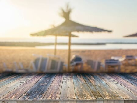 Wooden board empty table in front of blurred background. It can be used for display or montage your products. Sandy beach, umbrella palm leaves,crystal sea and the sun is in the summer background